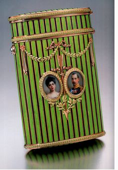 Cigarette case commemorating the wedding of Grand Duchess Elena, the Vladimirs' daughter, & Prince Nicholas of Greece & Denmark. Fabergé by workmaster Michael Perkin,1902. Decorated with alternate stripes of opaque green & mauve enamel. On the front are applied miniatures of the royal couple, by Zengraf, flanking Cupid's arrow below a ribbon-tied festoon.