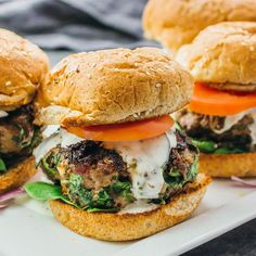 These healthy Greek burgers are made using ground beef mixed with spinach, feta, and sun-dried tomatoes, plus drizzled with a delicious tzatziki sauce.
