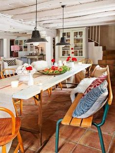 décoration maison de campagne - carrelage de sol terre cuite, table en bois à plateau blanc, chaises orange, coussins en rouge et bleu et suspensions métalliques noires