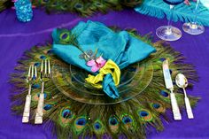Photo via Project Wedding.  Love the peacock feathers used to make a placemat or charger