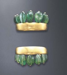 A STYLISH PAIR OF EMERALD AND GOLD CUFF BRACELETS, BY SUZANNE BELPERRON  Each polished gold rigid cuff, extending graduated tumbled emerald bead terminals, mounted in 18k gold, circa 1940, 2¼ diameter, with French assay marks and maker's marks With maker's mark for Sté Groene et Darde