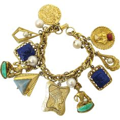 This is a vintage Egyptian Revival charm bracelet to add some fun to your day. The heavy gold tone chain has a mix of 10 charms and 4 dangling faux