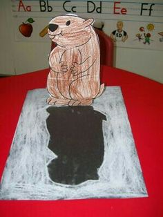 Ground hogs day craft have the child color and cut out their ground hog and then glue the extra flap to the paper and have them color around the groundhog in white chalk on black construction paper