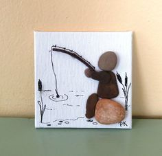 This original pebble art picture was created on 3x3 canvas board mounted on a small wooden easel. It was made with beach pebbles from Lake Michigan, twigs and ink. It features a man sitting on a rock fishing. This would make a nice Fathers Day gift. Buyer has the option of choosing a black or natural colored easel. Please specify your easel color choice when ordering. If not specified a random color will be selected. Thank you for looking and have a nice day.