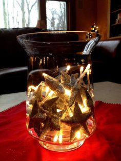 #DIY #centerpiece - Put individual silver glittery stars in a medium-sized glass candle holder with a small, battery-powered string of white lights!