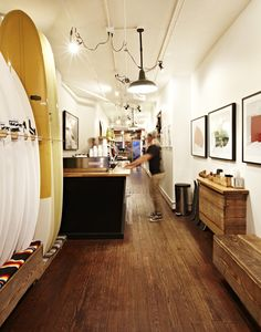"INSIDE SATURDAYS NYC A surf shop in New York City? Unexpected, sure, but also incredibly chic. Saturdays NYC was founded by three friends, avid surfers who ""saw a massive opportunity to bring the surf scene to the city,"" says co-founder Josh Rosen. Soho, Surf Cafe, Surf Store, Surfboard Rack, Surfboard Shapes, Opening A Coffee Shop, Surf Room, Saturdays Surf, Surf House"