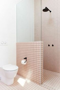 salle de bain italienne petite surface, carrelage mural e sol en rose et noir, douche et robinets en noir, petit meuble wc, douche isolée avec un demi-mur en carrelage et une moitié de verrière