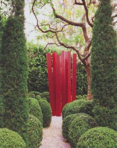 red sculpture at the end of a garden path