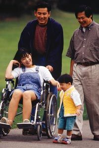 happy group of people on a walk; two adult men, a school-aged girl in a wheelchair, and a toddler.