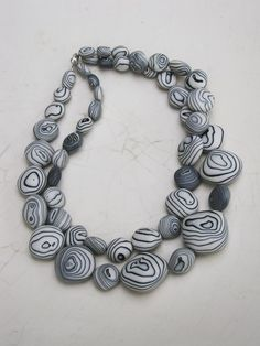 Don't the layered patterns of thesebeads remind you of stonesfound onthe beach? David Elliott, an Australian who'srelatively new to ceramic jewelry,made this necklaceout of vitreous porcelainand metal oxide pigments.