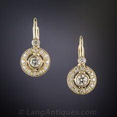 Sweet and petite. A pair of bright and sparkling, round collet-set diamonds float inside sparkling white diamond-set frames. Newly made in 14K yellow gold with lever backs. 5/8 by 5/16 inch.