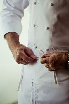 Photo Credit: William Hereford. Birmingham chef Frank Stitt ties on his apron and prepares for the day.