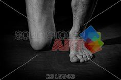 stock photo of the feet of a man standing on one knee