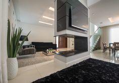 A sala de estar ganhou lareira revestida em pedra rústica, setorizando dois ambientes de estar.