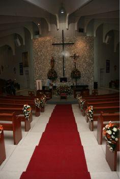 Corsages colocados en las bancas y en el altar unos arreglos grandes que deslumbran por la combinación de naranja y blanco.