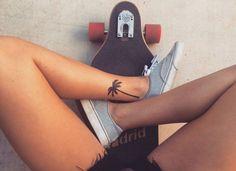 idée tatouage, planche à roulette en noir et rouge, baskets de toile gris pour femme, shorts courts en noir