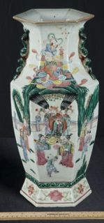 WONDERFUL TALL ASIAN THEME VASE WITH SCROLLWORK APPLIED ON EITHER SIDE AND A LOTUS BASE. DEPICTS CHILDREN AND ADULTS IN VARIOUS FORMS OF PLAY AND ENTERTAINMENT. MEASURES 16 INCHES TALL.