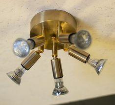Taklampa i obehandlad mässing med fem riktbara spotlights. Kan placeras vid takkontakt eller en bit ifrån, lampan är förberedd för båda alternativen.Mått
