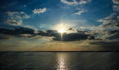 A beautiful landscape shot of the Solent, a strait at the Isle of Wight that separates the Isle from mainland England. The sun shining brightly in the sky forming crepuscular rays is beautifully reflected off the placid waters.