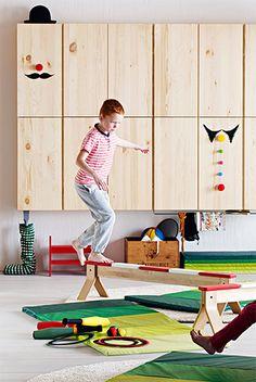 Un niño sobre una barra de equilibrios de IKEA en un espacio equipado con juguetes de gimnasia.