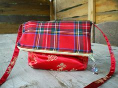 Folding clutch with shoulder strap. tartan wool blend & chinese satin. Zipper closure with pendant feature.