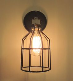 Industrial sconce wall light featuring a black cage and Edison bare bulb which is ready for a spot in a mudroom, bath or hallway. * 12 overall height and 4 3/4 wide Black Metal Cage * Projects out 6 from back wall * 5.25 Backer Plate * Hardwired installation * 60 Watt max. bulb * Edison Filament Bulb (Included) * UL Rated Components  Loft lighting at its best.  Arise, shine; for your light has come, and the glory of the Lord has risen upon you. Is.60:1