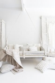 An old Indian baby swing we had refinished in white and piled high with our block printed textiles. Photography/Styling by Villa Styling.