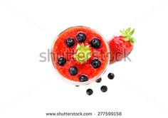 Fresh berries fruit and smoothies in tall glass on white . Blueberries and strawberries. Top View - stock photo