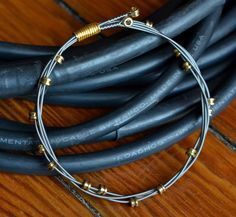 Recycled Guitar String Bangle with Brass Ball End 'Beads' Gift for musician or music lover. $22.00, via Etsy.