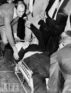 11/24/63: Mortally wounded, Lee Harvey Oswald is wheeled into Parkland Hospital.