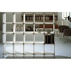 Endless Plastic Shelf Design: Werner Aisslinger  Manufacturer: Porro  Bookcase based on self-supporting panels in natural Metacrilate (PMMA), linked together by special die-cast joints. Turned aluminium support feet with level adjuster knob.