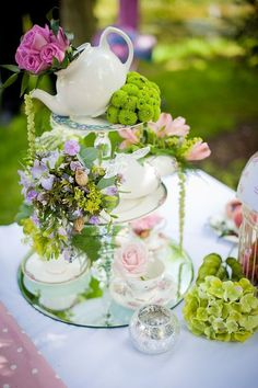 Tea:  A beautiful tea-time centerpiece, with an artfully arranged teapot and flowers.