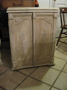 """Old treadle sewing machine cabinet painted in ASCP Old White with heavy dark wax treatment and clear wax final coat.  Very awesome...I've taken this reinvent a step further by having a tin """"dry sink"""" installed where the sewing machine would have """"popped""""up and have reinvented same as a liquor/bar cabinet.  Very cool."""