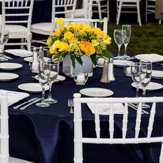 The simple centerpieces really pop with the navy table covers. And it all comes together with the white place settings, making for a clean and elegant look. Image Credits: Shoreshotz1 Photography