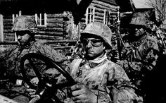 This close-up shows a three-man Schwimmwagen team wearing typical SS camouflage. The skull on the driver's right collar patch identifies these men as members of the Totenkopf Division. They were photographed driving through the Baltic states on their way into the Leningrad area during Operation Barbarossa.