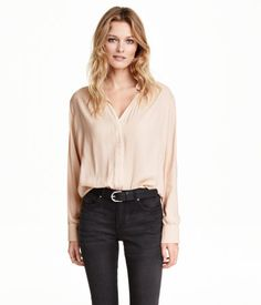 Wide-cut blouse in lightly crêped woven fabric. V-neck, concealed button placket at front, long sleeves with buttons at cuffs, and slits at sides. Rounded hem, slightly longer at back.