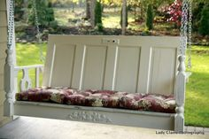 Beautiful porch swing made out of a repurposed door, and old table top and a headboard.