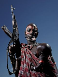 Mursi mother with child and gun! Photo by Neil Thomas — National Geographic Your Shot