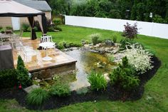 In this photo we see a beautiful patio made of yellow travertine paving stones in Wyandanch, New York (11798). Yellow travertine is the perfect paving stone for you if you love color;  in this photo.  On top of this patio we see many different types of outdoor furniture to overlook and enjoy your backyard. To the side of the patio there is a breath taking pond with tons of different types of landscaping features. This pond is the perfect water feature to enjoy with family and friends to…