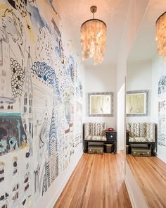 This long entry hallway was dark and foreboding before a remodel. The solution was a large mirror, delightful wall mural and whimsical pendant light fixture that livened up and infused an eclectic vibe into the neutral entryway.