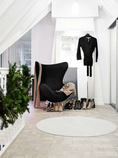 En stilfull, svart stol er omringet av lekre damesko og klesplagg, og skaper et lite motehjørne i andre-etasje.