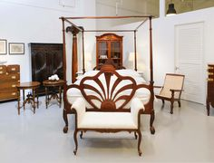 All British colonial, lovingly restored, antique furniture made during the late 19th century in India! A mahogany four poster bed, a display cabinet, a newly upholstered window seater and an original planter's chair. The rosewood cupboard in the back features a sunburst carving. One by one, stunning pieces!