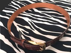 Made of embossed calf skin (saddle leather quality) and leather-lined, this textured Vintage Embossed Brighton Belt with a bright-gold buckle is nothing short Brighton Belts, Vintage Designer Clothing, Saddle Leather, Emboss, Vintage Leather, Saddle Bags, Vintage Outfits, Brown, Silver