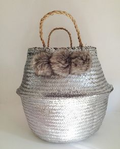 Beautiful and practical silver handwoven sea grass basket with six grey faux fur pom poms.  These beautiful baskets have so many uses and make