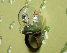 A scene from Alice in Wonderland is sculpted in polymer clay under a glass dome on an adjustable brass ring.