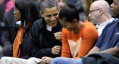 Caption: President Obama shares a light moment with the first lady during an NCAA basketball game between Oregon State and Towson in Towson, Md.