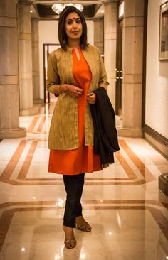 Worry no more to look suited up in an Indian look to work. Here's a beautiful jute jacket teamed up with pretty orange silk kurta and mul silk black straight pants.