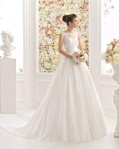 Vestido de corte clássico confecionado com corpo de renda e brilhantes e saia de chiffon, com decote tipo barco e costas baixas com flor, em cor natural.