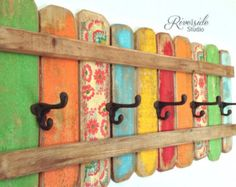 A unique original wood coat rack with rusty-looking cast iron hat and coat hooks. A cheerful display painted in green, yellow, blues, red, and floral then distressed and protected. Organize your home with this one of a kind beautiful rack. I make these colourful coat racks in my woodshop and each one has unique character and charm. The back has 2 strong metal, keyhole hardware brackets already attached 16 apart. Perfect for the bathroom, bedroom, or hanging backpacks and coats by the door…