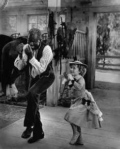 """Bill Robinson and Shirley Temple in a scene from The Little Colonel, a 1935 feature film starring Shirley Temple, Bill """"Bojangles"""" Robinson, Lionel Barrymore and the Academy-Award winning actress Hattie McDaniel. Vintage African American photography courtesy of Black History Album, The Way We Were. Follow Us On Twitter @blackhistoryalb"""
